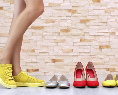 Woman choosing shoes on brick wall background